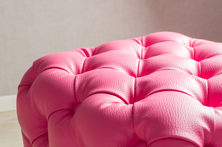 Pink pouf, furniture with decoration buttons in the home interior.