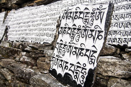mantra: CHAURIKHARKA, NEPAL - CIRCA OCTOBER 2013: Mani stones with the inscription mantra is one of the elements of the Buddhist religion circa October 2013 in Chaurikharka.