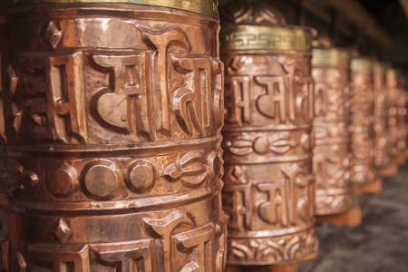 rotational: PANGBOCHE, NEPAL - CIRCA OCTOBER 2013: prayer wheel used in Tibetan Buddhism to the rotational axis of the cylinder inscribed with mantras surface circa October 2013 in Pangboche. Stock Photo