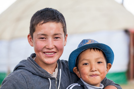 SONG KUL, KYRGYZSTAN - CIRCA JUNE 2017: Children of one of the camps at Song Kul  high alpine lake in the Tian Shan Mountains of Kyrgyzstan circa June 2017 in Song Kul.