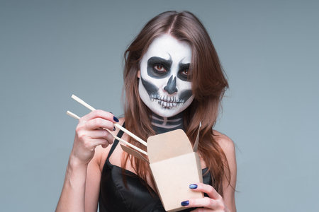 Young beautiful girl with a sugar skull make up, holds in her hand a paper box for instant noodles and chopsticks. Halloween face art on gray background.