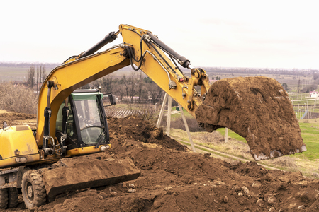 Excavator digging to moving the soil to the truck and adjusting ground level in construction site. Stockfoto