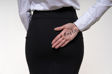 Assistant girl hides behind her hand a hand with an inscription me too. Sexual harassment and abuse at work concept. Physical fight at workplace. Archivio Fotografico - 110134326
