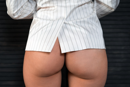 Beautiful sexy young pop-young woman in an office jacket on a background of black blinds. Luxury ass. Huge Butt. Sexual forms. Big ass. Sports figure. Round buttocks. Sex affair at work