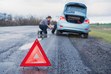 The man is changing the damaged wheel of the car on the roadside of a bad road after the rain against the background of an orange  emergency  triangle warning Reklamní fotografie