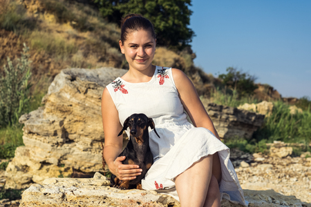 Beautiful girl with her dog dachshund, black and tan, rest on a stone beach against a blue sky. Standard-Bild - 110134337