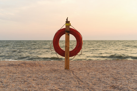 Sunset on the sea and the orange lifebuoy on the beach