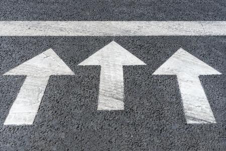 White arrows on black highway asphalt, pedestrian crossing road marking fragment Reklamní fotografie