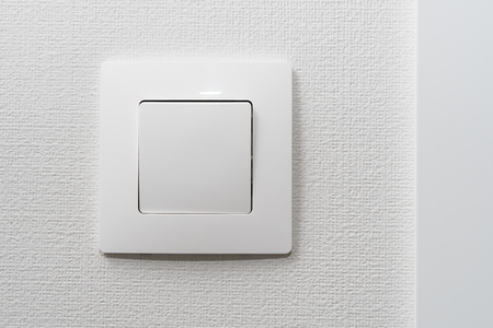 Simple white light switch, turn on or turn off the lights hanging on the white wall in the room