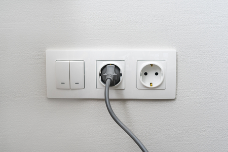 Electric light switch and socket on the empty wall, electrical power socket and plug switched. The concept of energy savings.