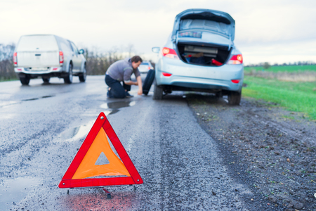 road accident sign on the background man replaces flat tyre on road. Car tire leak because of nail pounding. Reklamní fotografie