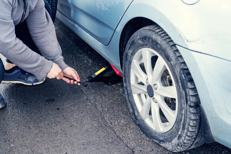 man replaces flat tyre on road. Car tire leak because of nail pounding.