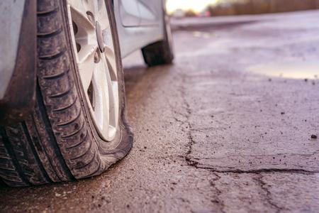 Llanta pinchada en la carretera. Fuga de llanta de automóvil debido a golpes de uñas Entonado Foto de archivo