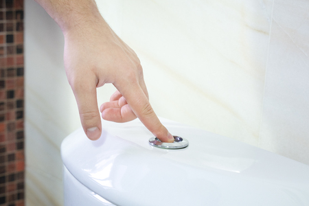 Finger pushing a flush toilet button for cleaning. Full discharge button