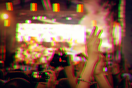 Audience with hands raised at a music festival and lights streaming down from above the stage. Digital signal  glitch effect (rgb shift, slices). Screen error