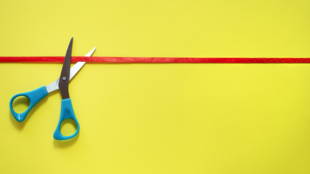 Grand opening. Scissors cut the red ribbon on yellow background, top view. grand opening idea, sign, symbol, concept