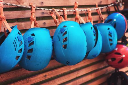 Kletterausrüstung - blauer Helm hängt an einem Brett in einem Seilpark