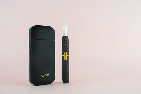 ROSTOV-ON-DON, RUSSIA - January 03, 2019: Newest  IQOS electronic cigarette (heating tabacco system) on pink backgrounds.