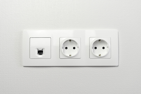 Electrical sockets on the wall with black connection internet plug and white wire. Socket set with usb cord and electricity cable with selective focus on neutral background.