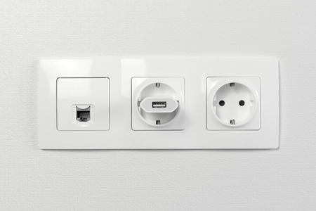 Electrical sockets on the wall with black connection internet plug and white wire. Adapter from the charging device with usb input plugged in Фото со стока
