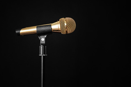 gold microphone on stage on a black background