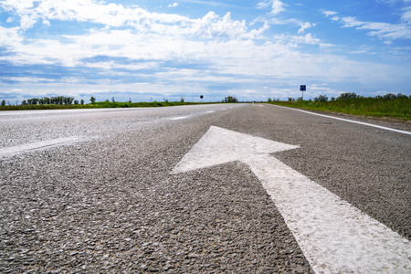 Forward igns on the road. White painting in turn left direction arrow symbol on black asphalt road background and against the blue sky Imagens