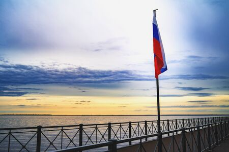 Russian tricolor flag flying in the wind in the port of marina at sunset