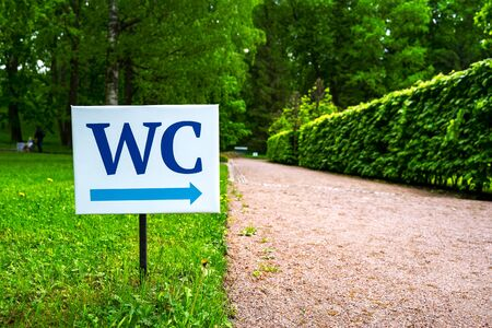 toilet sign against the background of green trees in the park.  White WC sign on white metal plate with blue pointing arrow indicating the direction