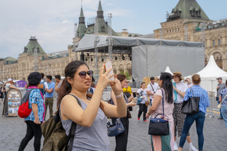 MOSCOW, RUSSIA - JUNE 04, 2019: A female tourist takes pictures on her smartphone sights on Red Square in Moscow