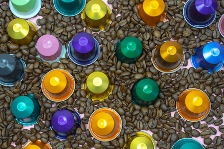 Multicolored coffee pod capsule on coffee beans close up