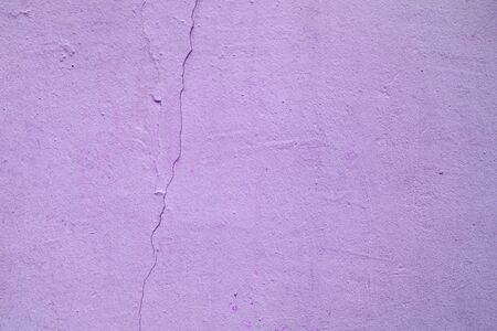 Old purple wall with crack and plaster. textured background