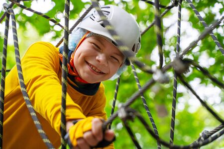 Active brave little boy enjoying climbing at treetop adventure park and smiles