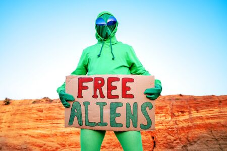 a man dressed in a green alien carnival costume suit at a lone rally with a sign