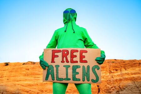 a man dressed in a green alien carnival costume suit at a lone rally with a sign free aliens on the background of a desert canyon Stock Photo