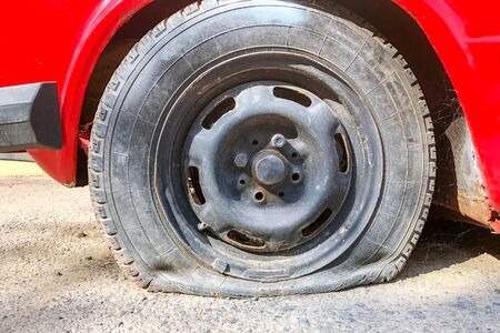 Flat tire of red car on the road waiting for repair. Flat tyre on road. Car tire leak because of nail pounding.