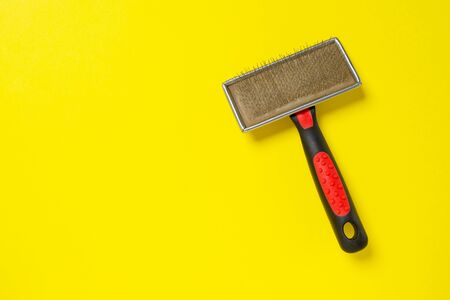 Grooming brush, or professional comb for dog on bright yellow background.