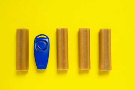 Some sticks of dog delicacy and clicker, special training appliance, on bright yellow background. Pet train or handling concept.
