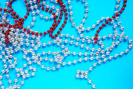 Red and white beads on bright blue background. Christmas or New year tree decoration, home holiday.