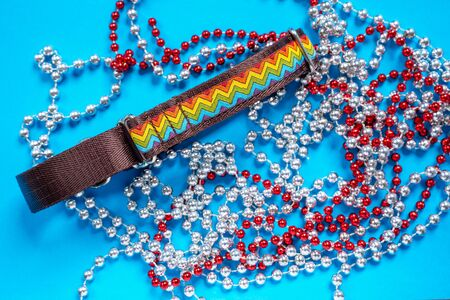 top view  сolorful dog collar and leash from silky tape, red and white beads on blue background, copy space.  Christmas or New year tree decoration, home holiday. Zdjęcie Seryjne