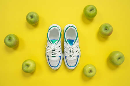 Top view of empty white sneakers with blue and green decorations on the edgings, setting on the center of the shoot with fresh green apples at around. Studio, bright yellow background, copy space.