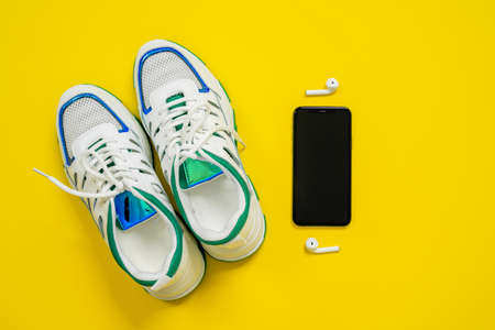 Top view of empty white sneakers with blue and green decorations on the edgings, black mobile phone and white wireless earphones on bright yellow background. Walking or hiking concept, copy space.
