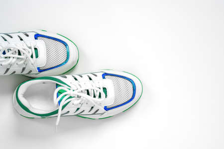 Top view of empty white sneakers with blue and green decorations on the edgings, setting on left side of the shoot. Studio, isolated, white background with copy space.