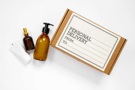 The cardboard box with label written about personal delivery and some cosmetic treatment bottles, on white background with copy space for any text. Post or courier service concept.