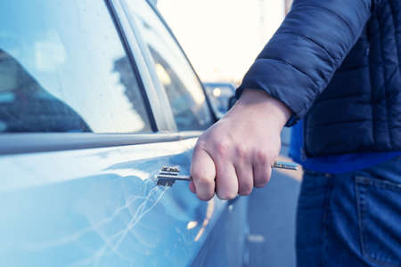 Bad guy scratching the car door with a key in the parking lot on the street. Damage of property from revenge for treason or betrayal, or threat. Auto insurance fraud or vandalism.