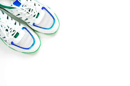 Clean stylish sneakers decorated with blue and green shiny lines stand in the corner of frame on white background, top view, copy space. Studio shot for new shoe advertising banner