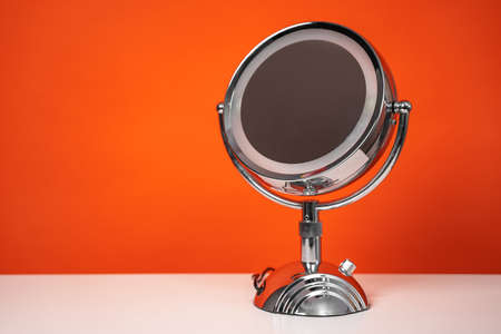 Round mirror on metal stand with backlight stands on table on orange background, copy space for text, front view. Beauty equipment for makeup artists and cosmetologists for use at home 写真素材
