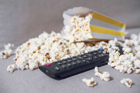 The cardboard box with popcorn and remote control on gray background. Concept of hobby or pleasant time spending at home, watching movie. Indoors.