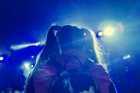 A little girl with two ponytail sits on her father's shoulders at a rock concert in the spotlights, illuminated by blue spotlights