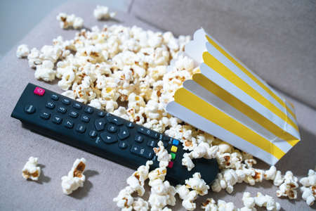 TV remote in heap of salty or caramel popcorn spilled from striped paper box. Relaxing evening after hard working day watching show, movie or sports program. Junk food and unhealthy nutrition, snacks