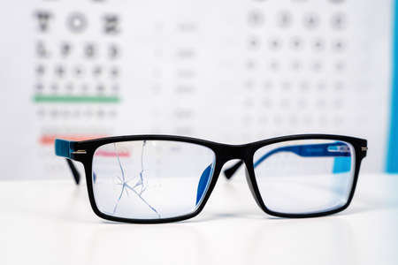 close up of broken black glasses and snellen chart hanging on the wall in the ophthalmologist office.